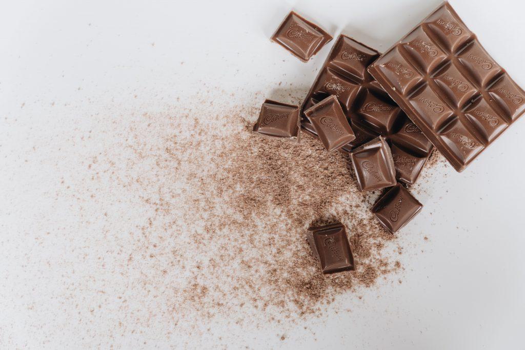 Milk chocolate bar on white surface. (Image courtesy of Alleksana)