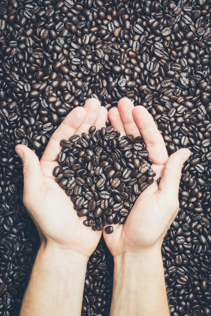A person holding coffee beans (image courtesy of Magic K)