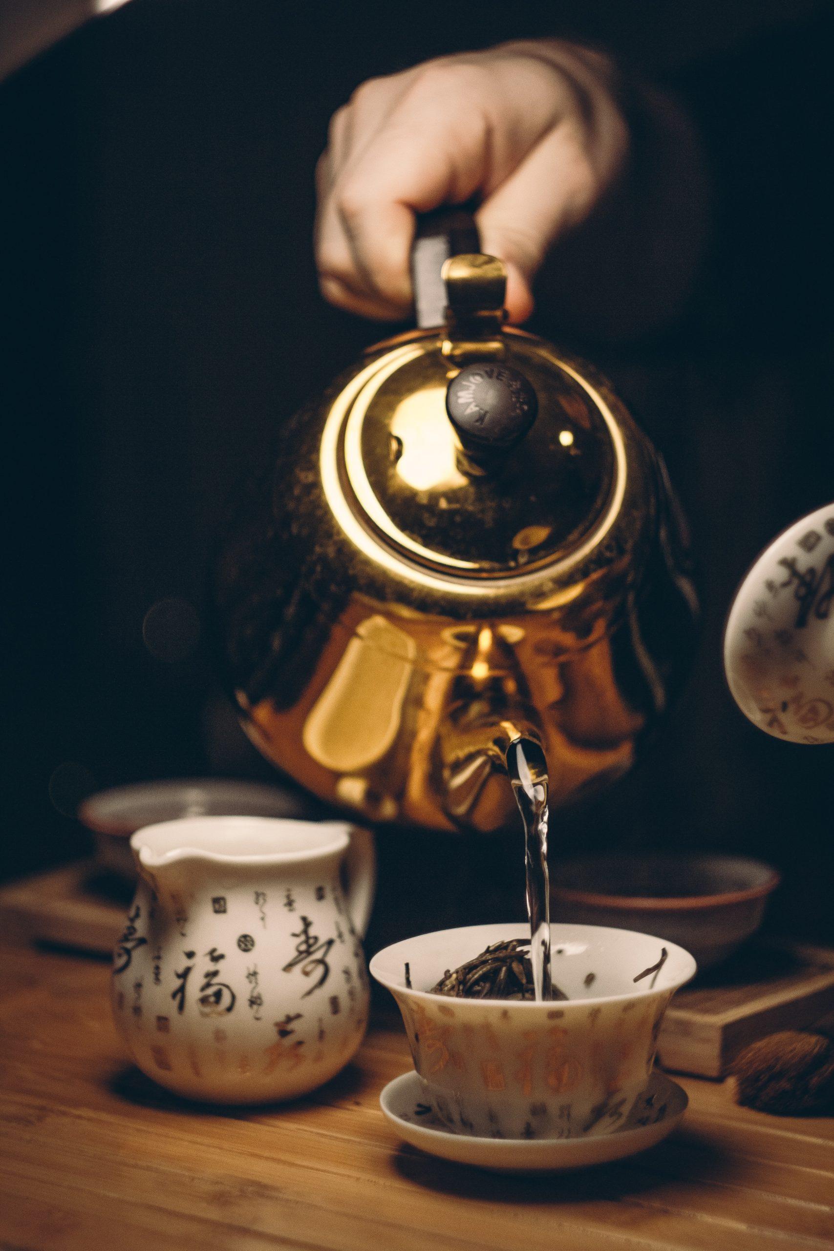 Person Holding Gold Teapot Pouring Into White Ceramic Teacup (Image Courtesy of Nikolay Osmachko)